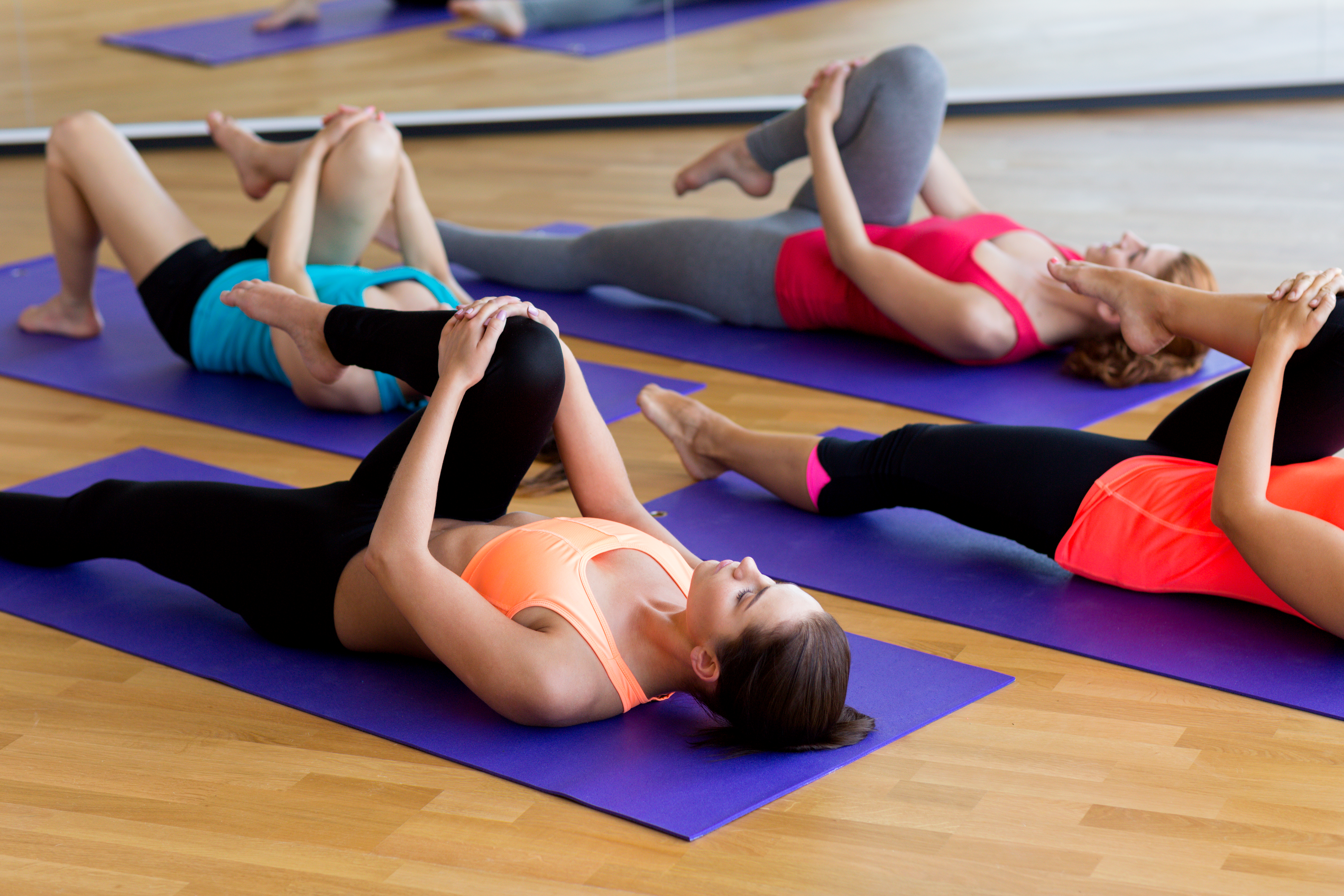 fitness, sport, training and lifestyle concept - group of women stretching in gym